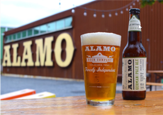Picture of a Alamo draft house brew in front of one of it's locations.