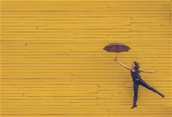 Young woman jumping gleefully with an umbrella against a bright yellow wall. Photo by Edu Lauton.